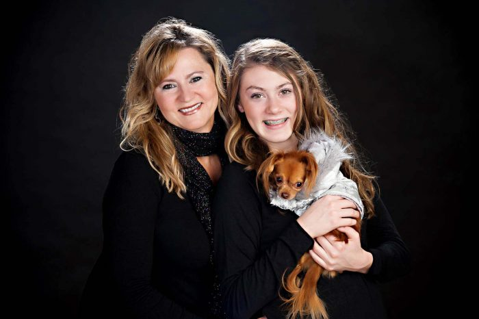 family studio portraits of mother and daughter holding a little dog