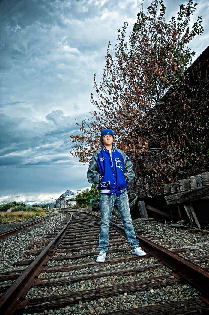 senior-picture-boy-in-blue-letterman's-jacket-stnading-on-railroad-tracks