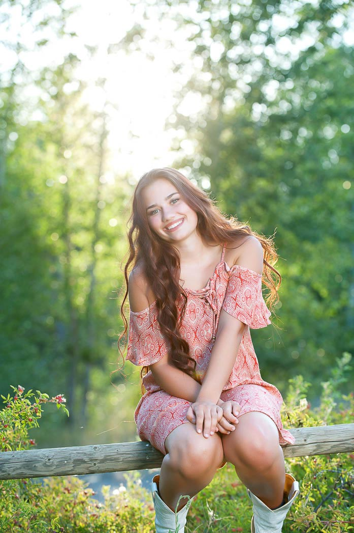 girl-sitting-on-fence-with-sunlight-during-country-girl-senior-portraits