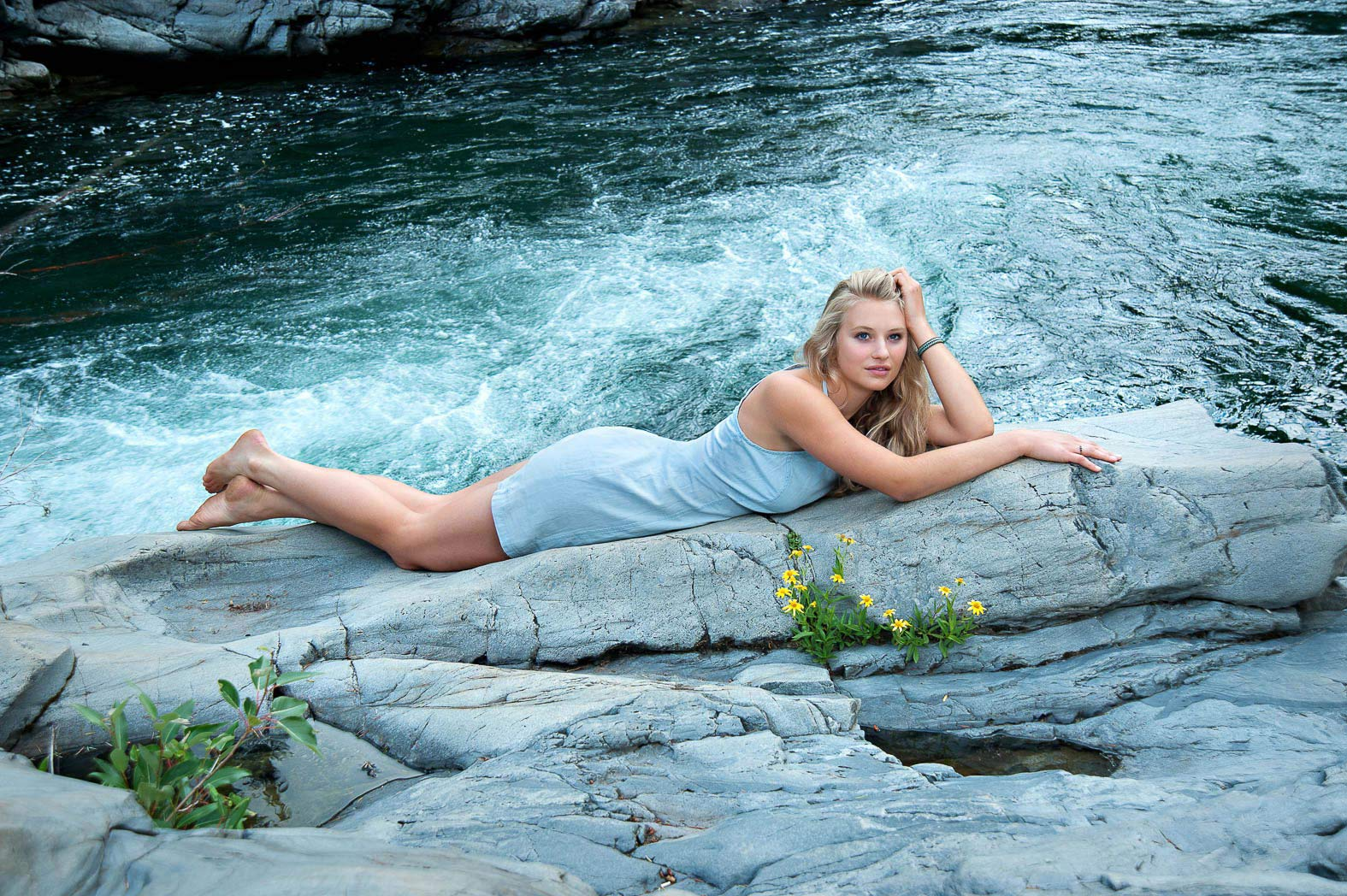 girl-laying-by-river-during-enchanted-senior-pictures