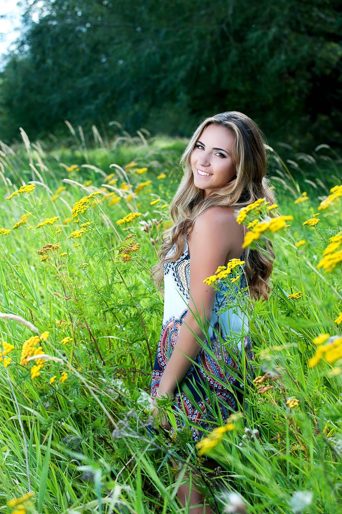 senior girl smiling in meadow of yellow flowers