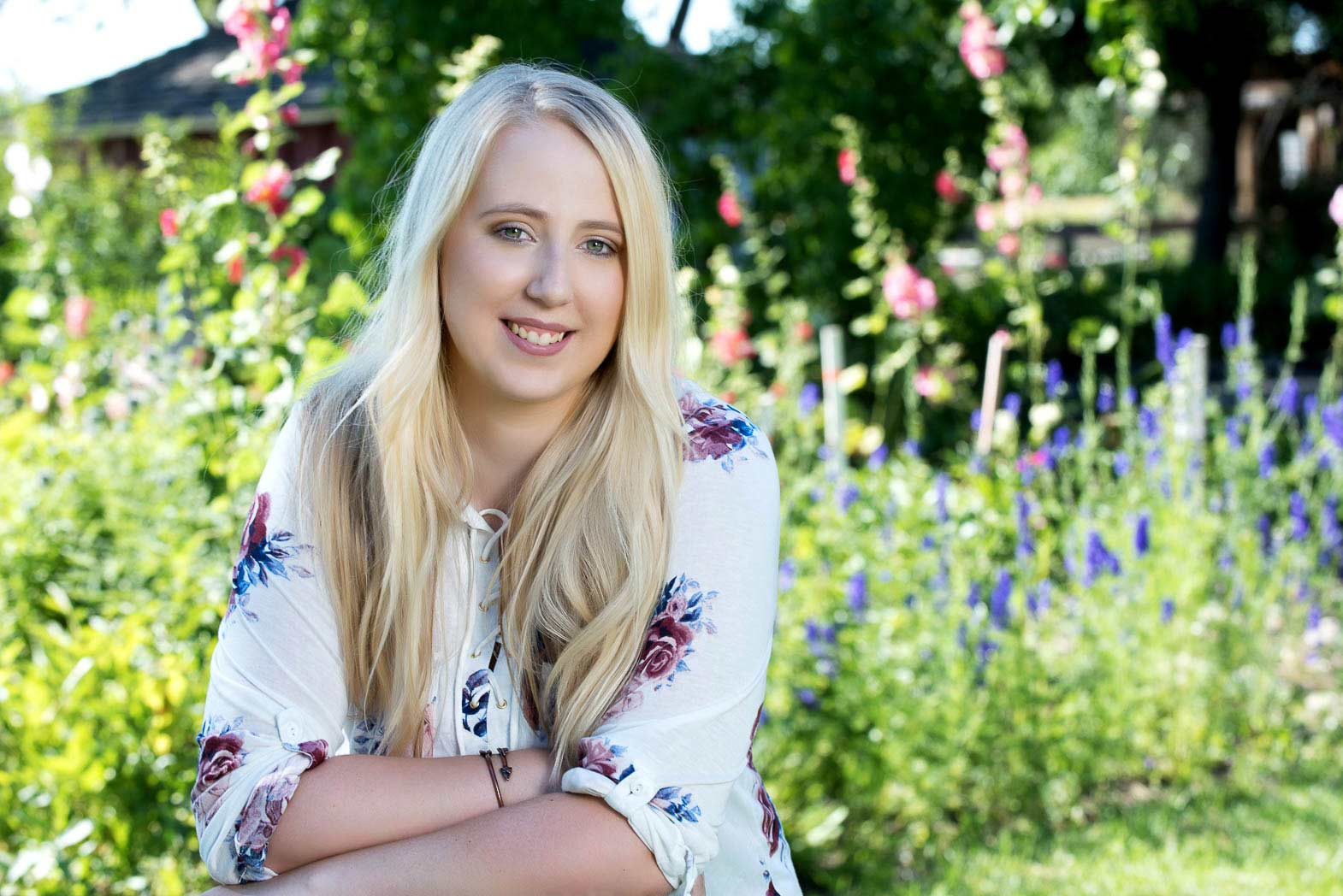 country girl senior picture of blond smiling in front of flowers and summer garden