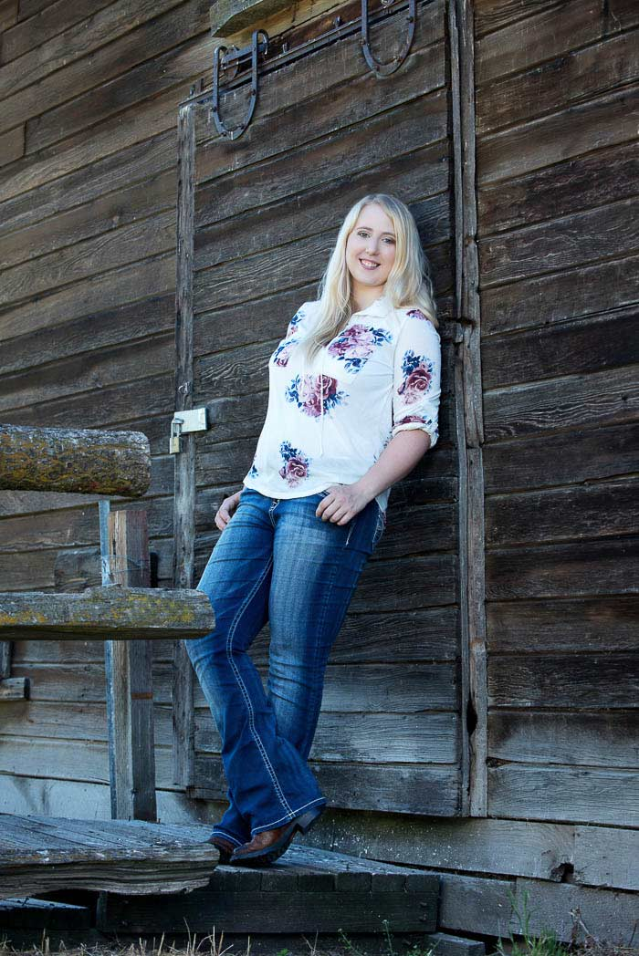 senior picture of girl in boots and jeans leaning against an old barn