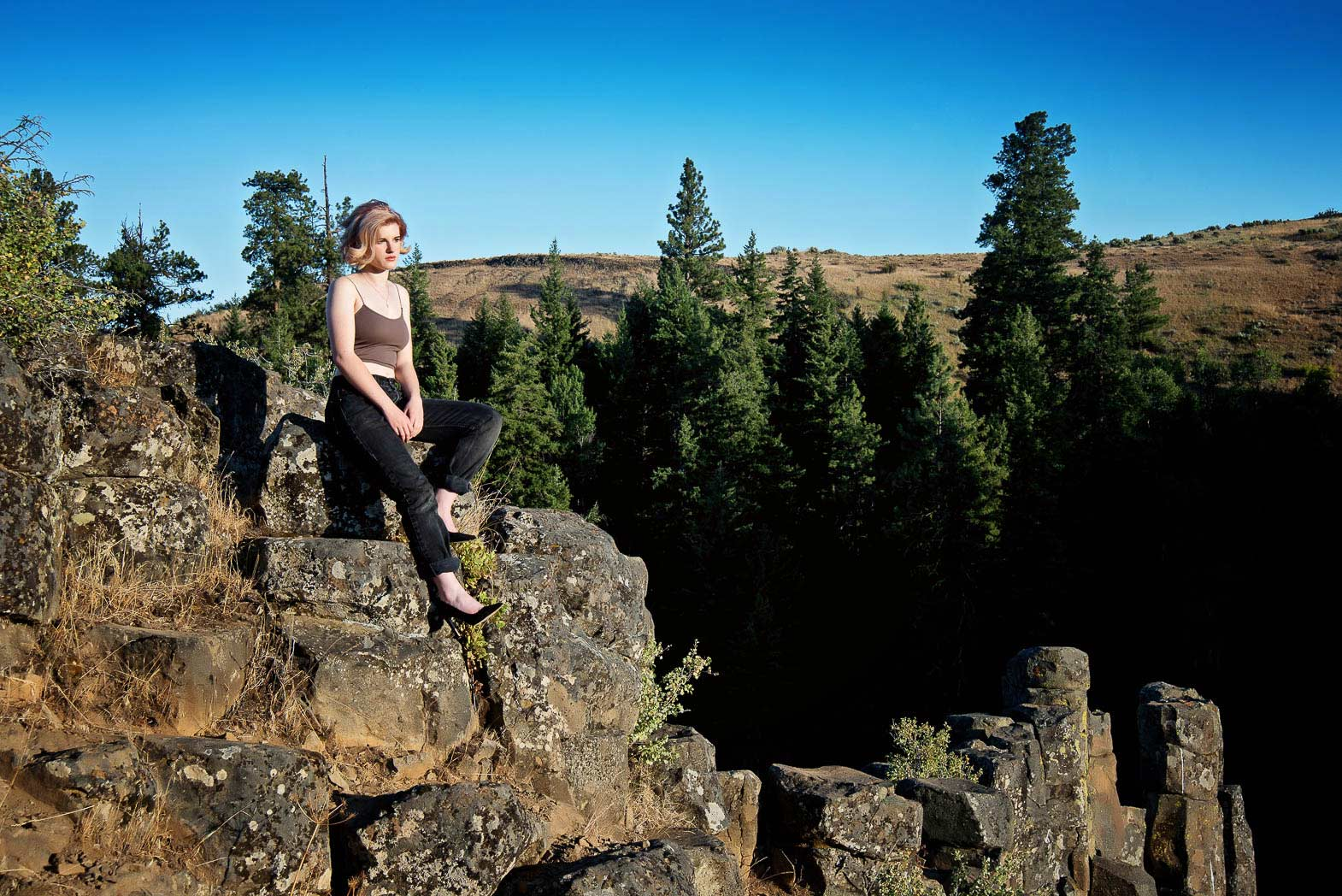 wilderness senior picture of girl sitting on top rock cliff