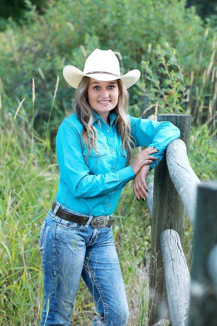 cowgirl senior picture of girl leaning on a pole fence