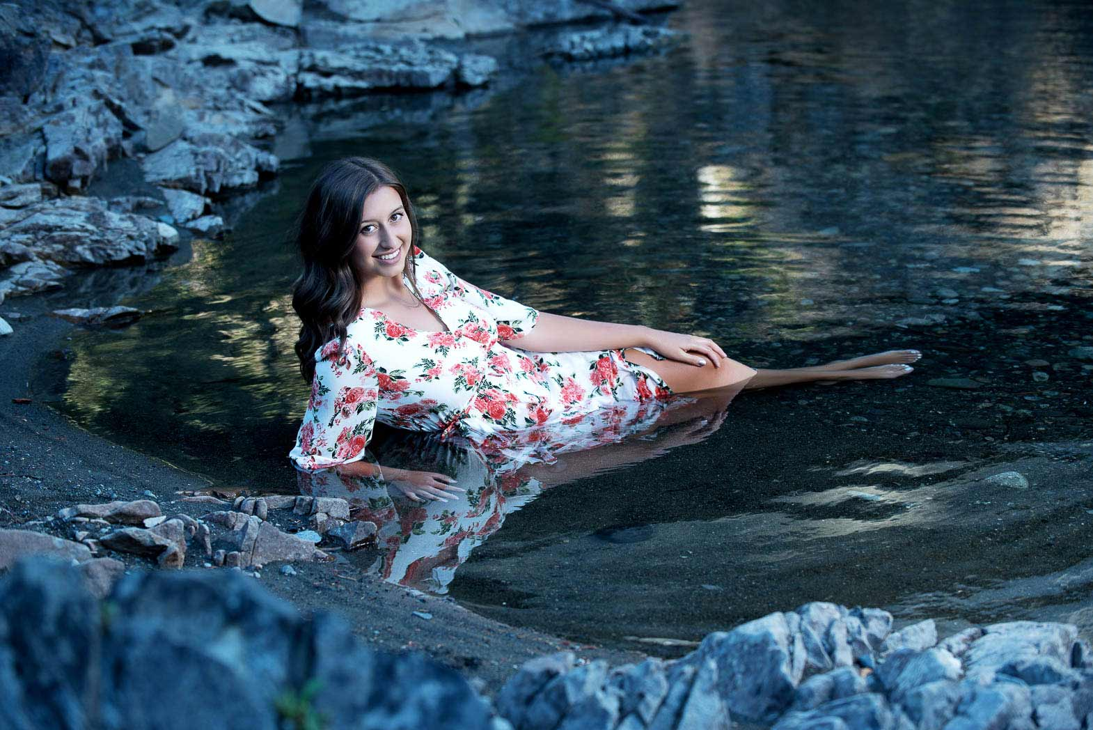 senior picture of girl wearing flowered gown lying in clear mountain water during her forrest senior pictures