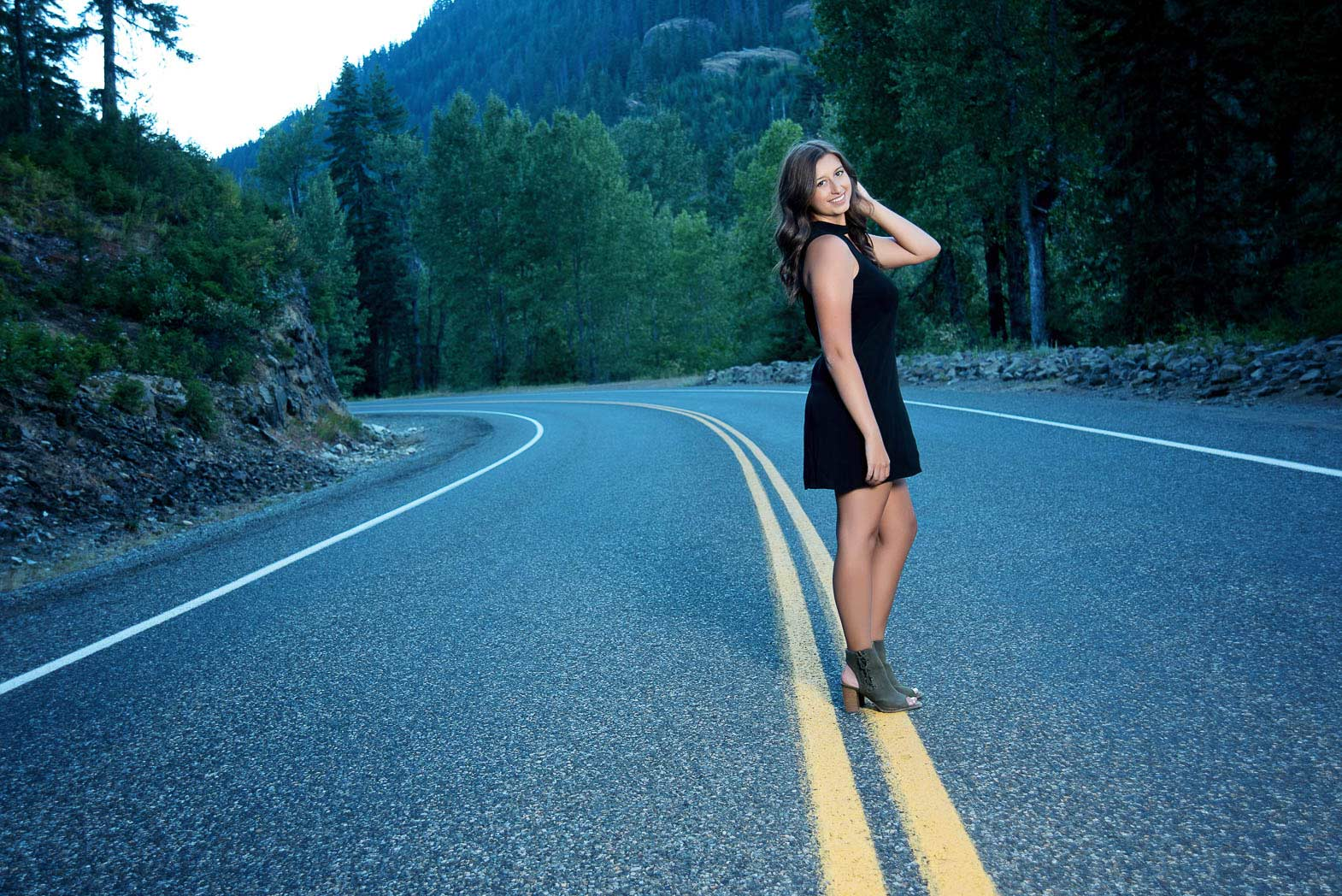 senior girl standing on yellow midline of mountain road