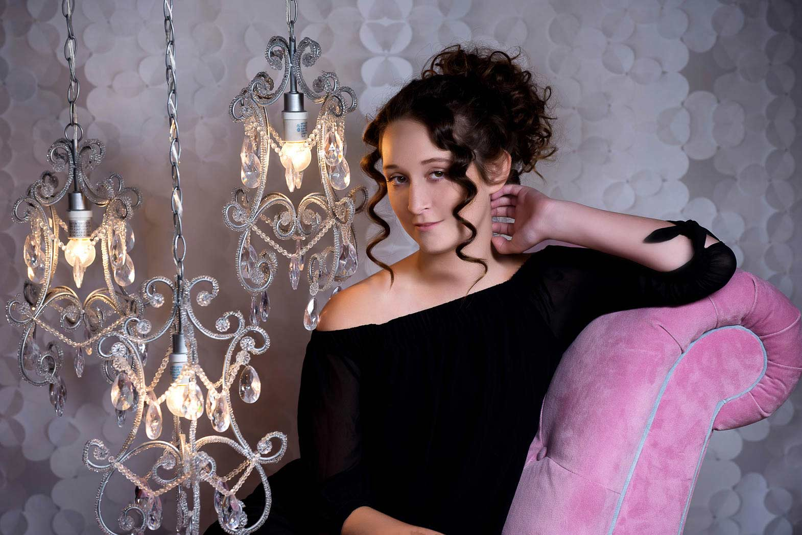 senior girl sitting by chandeleirs on pink sofa