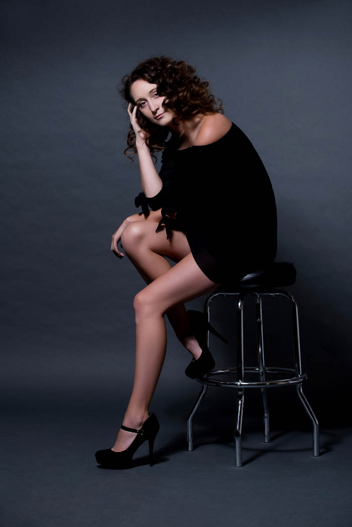 moody senior picture of model sitting on metal stool
