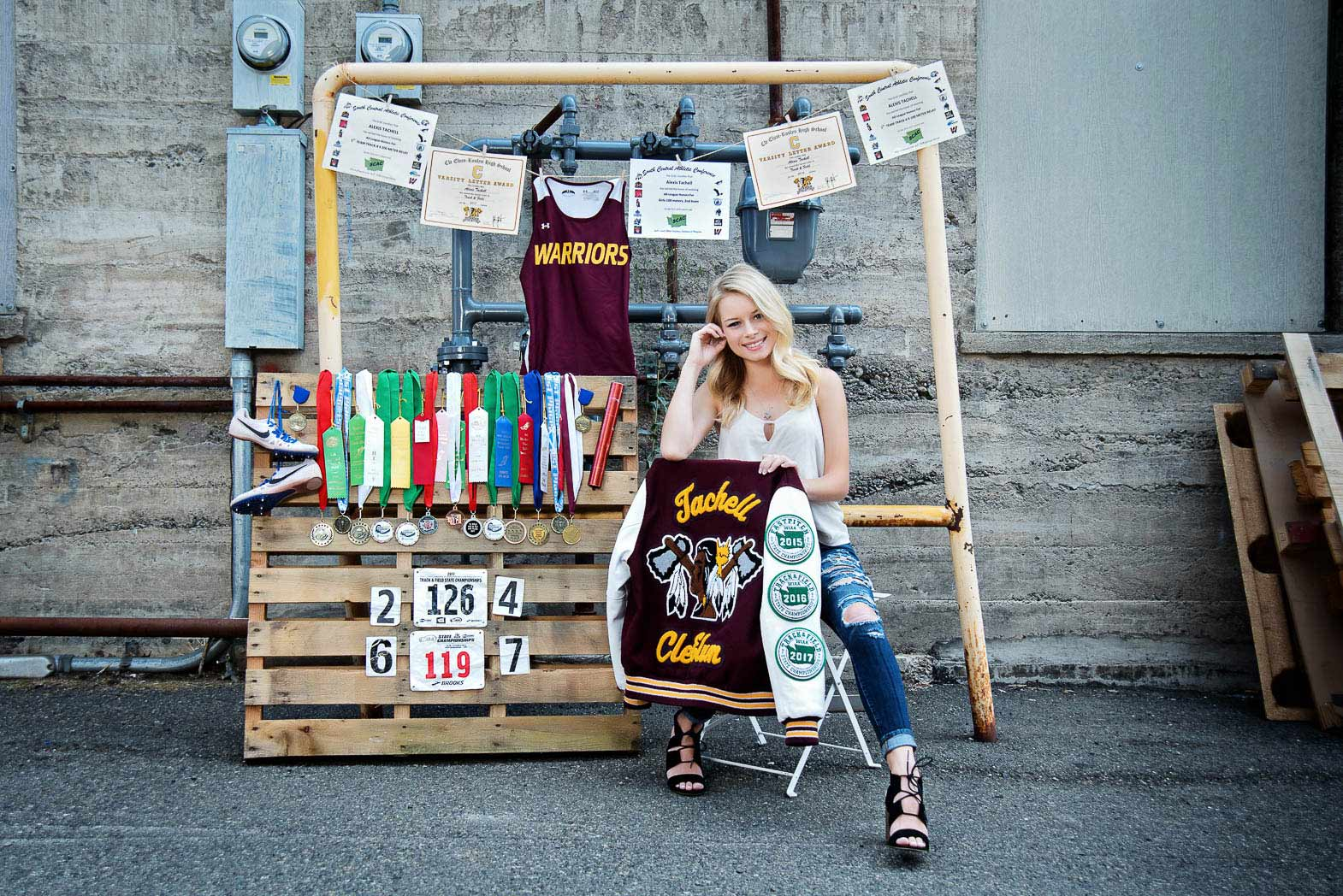 senior model sitting in front of display of all her high school medals and awards