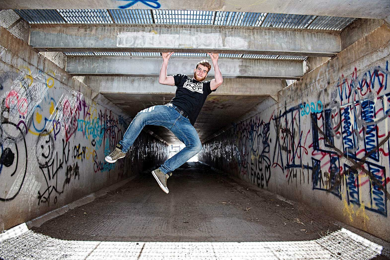 exciting senior picture session with boy swinging from roof of graffiti covered tunnel