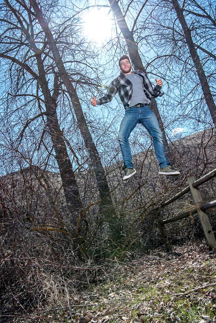 young man jumping very high in fron of trees during his exciting senior picture session
