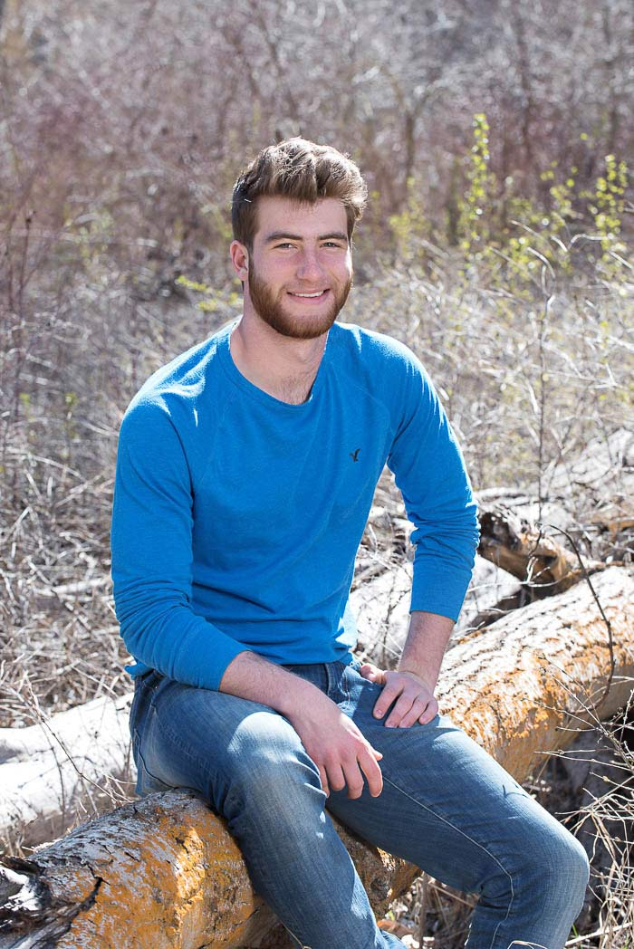 young man smiling while sitting in the woods during exciting senior picture session
