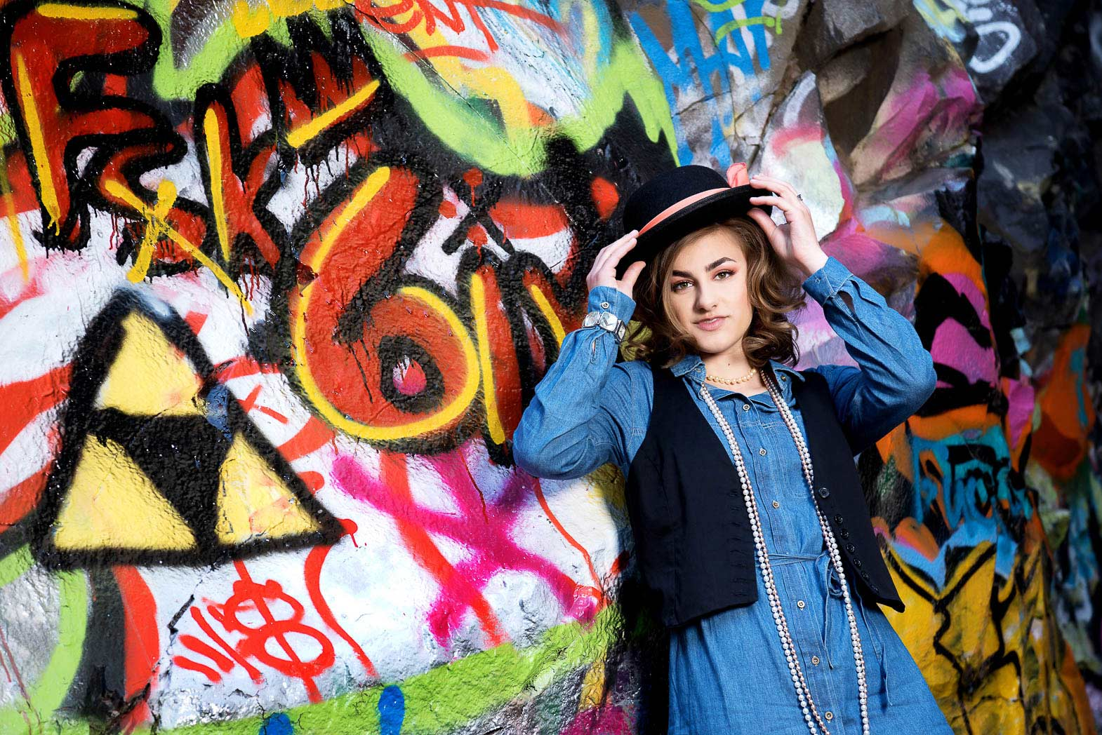 senior model shoot girl lifting hat by graffiti