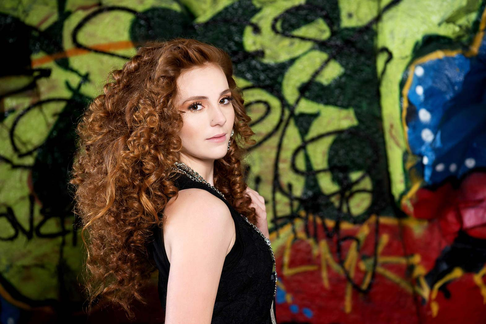 red haired senior model standing in front of graffiti looking over her shoulder
