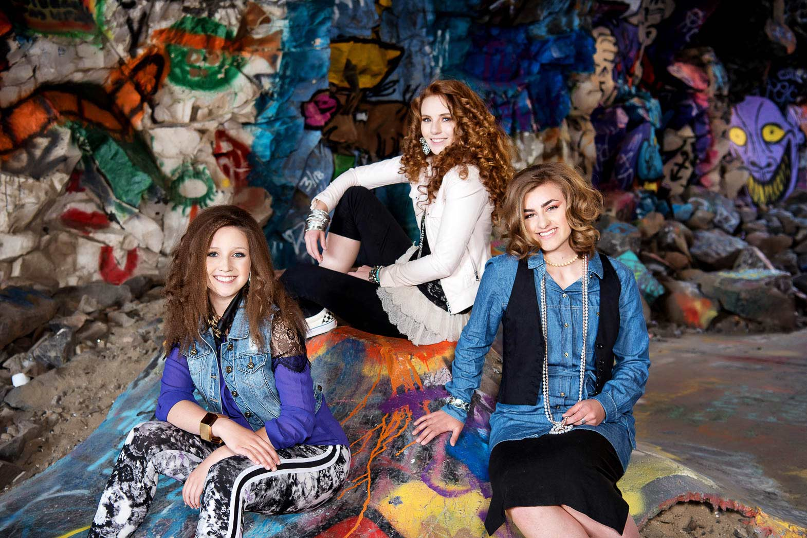 senior model group sitting together in graffiti tunnel