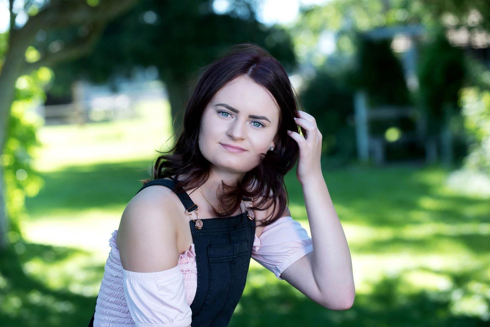 girl in park holding back her hair as she smile in senior picture