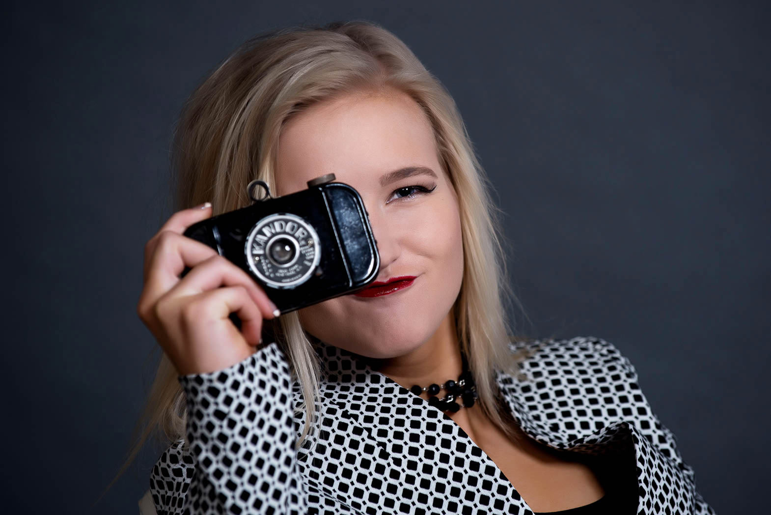 senior girl smiling holding a vintage camera during studio model shoot