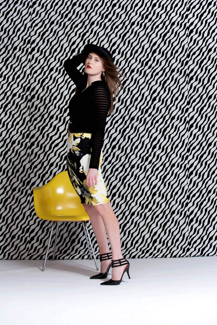 senior girl posing with yellow chair during black and white studio model shoot