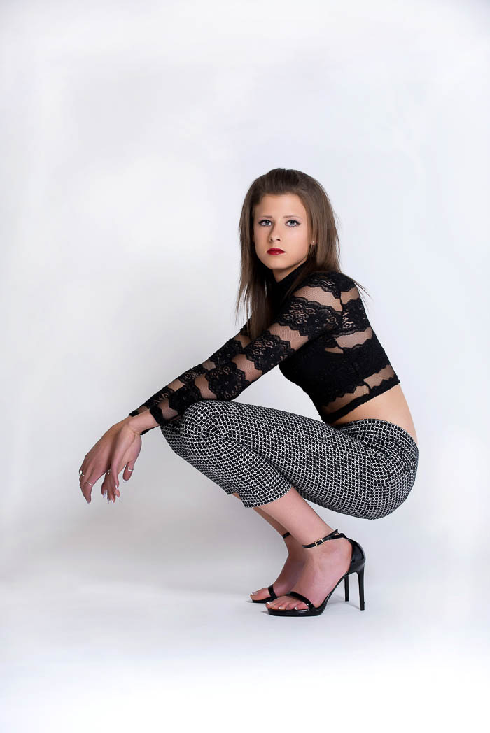 senior girl posing during studio model shoot wearing black and white