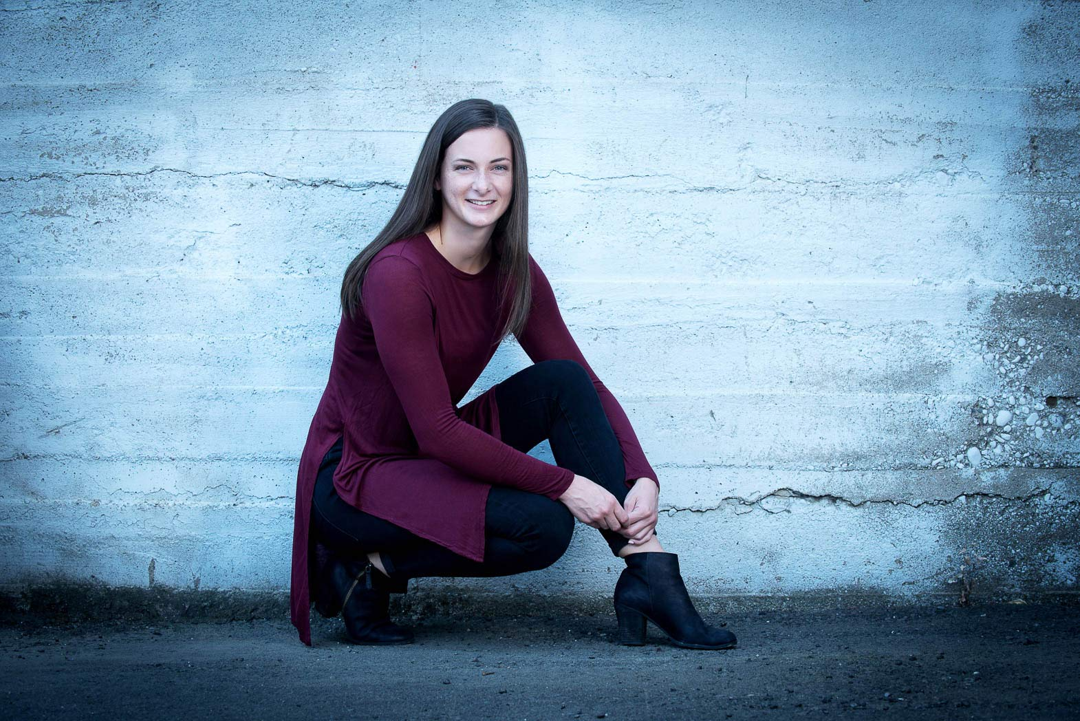 fashionable senior picture of girl crouched down smiling
