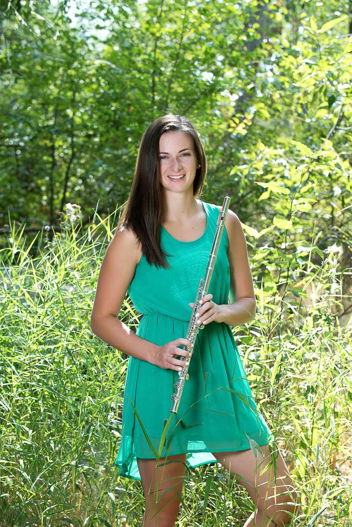 musical senior portrait of girl holding flute surrounded by green grass and trees