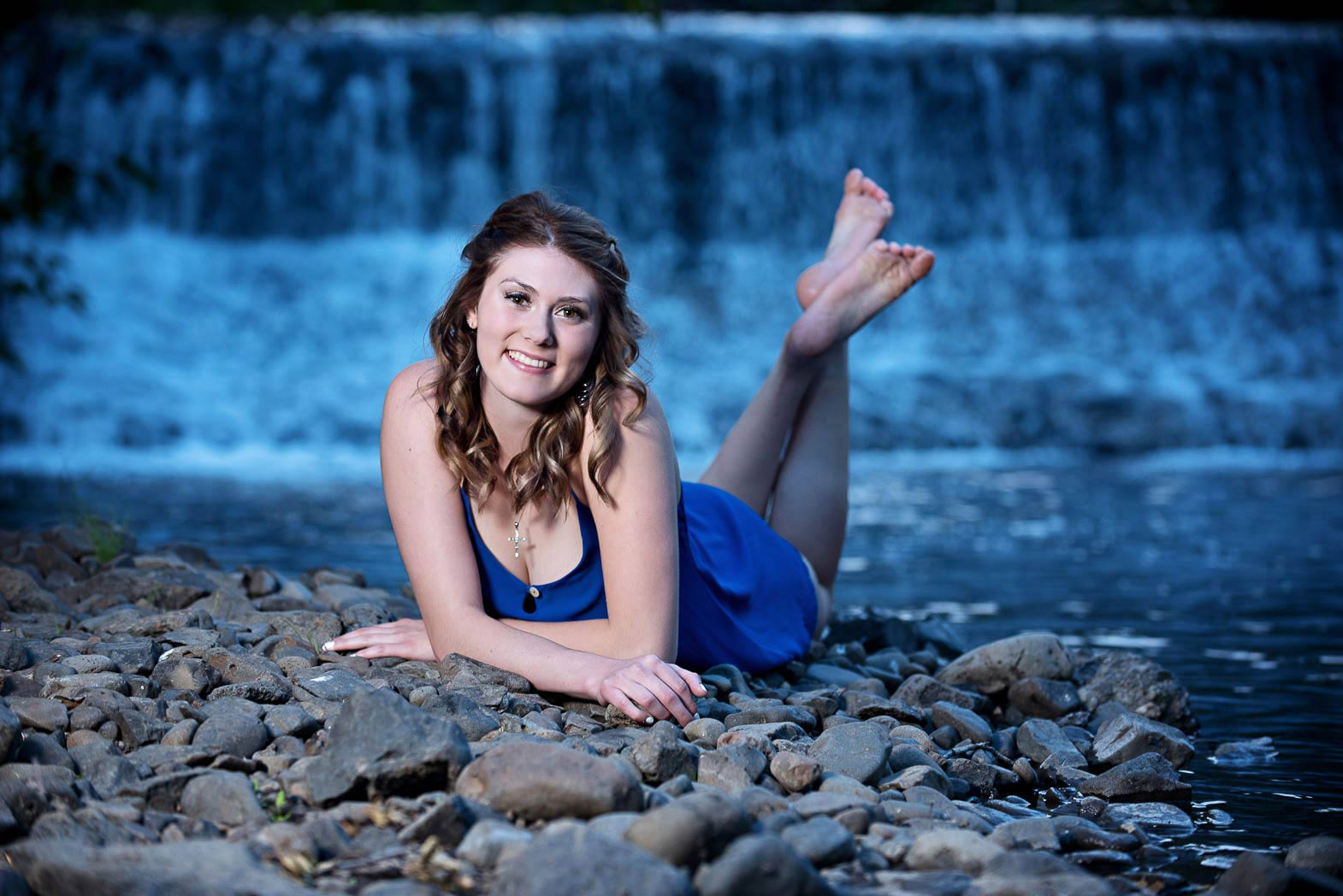 waterfall senior picture of girl laying by river with waterfall in background