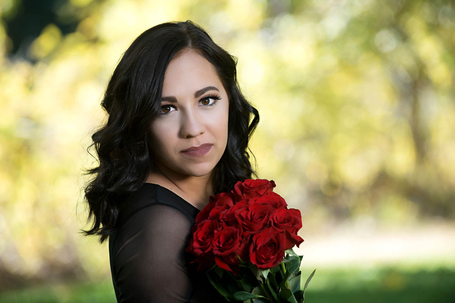 girl holding bouquet of red summer roses for senior pictures