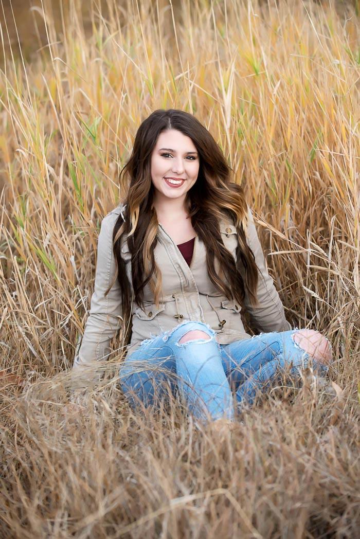 girl sitting in tall grass