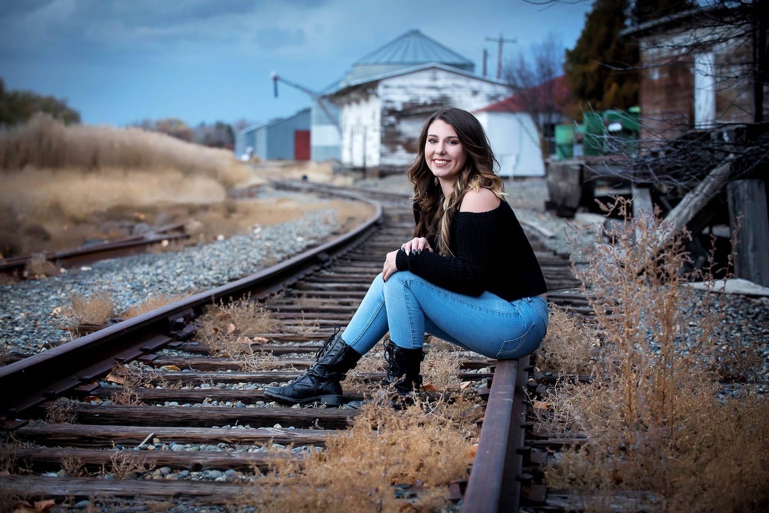 senior picture of girl sitting on old train tracks