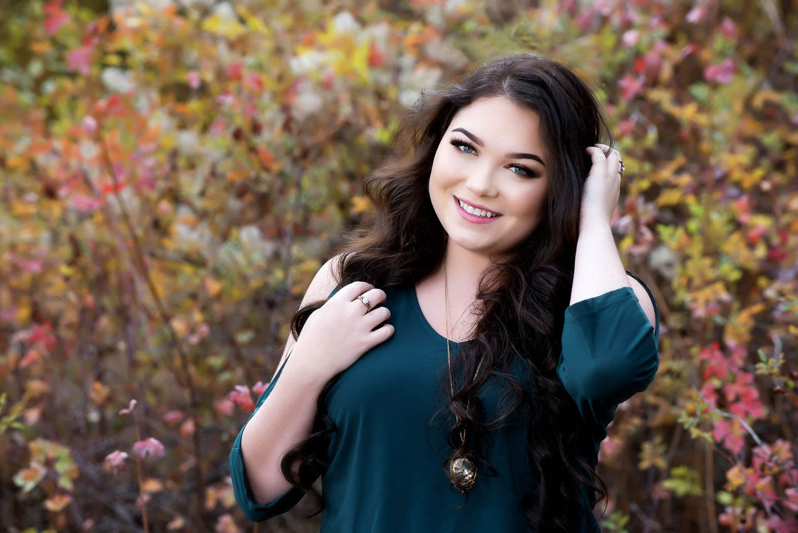 senior portrait of girl with hand in hair smiling with fall colored leaves behind her