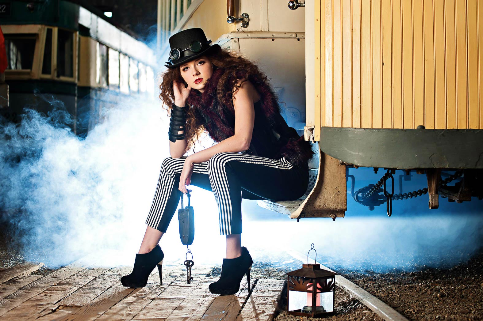 photonuvo-steam-punk-senior-model-dressed-steampunk-style-sitting-on-train-steps-surrounded-by-steam