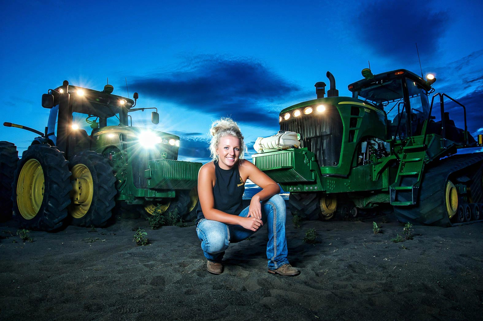 girl-sitting-by-big-green-tractors-night-sky-behind-during-country-girl-senior-pictures