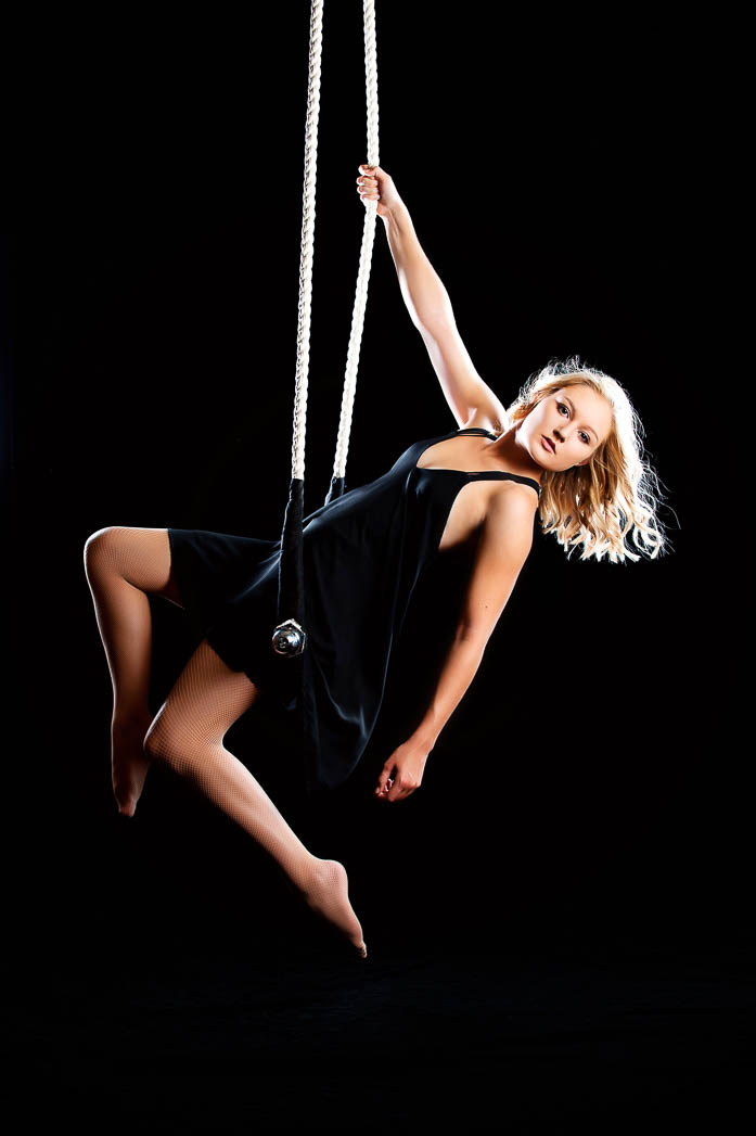 girl-on-trapeze-against-black-background-during-unique-senior-pictures