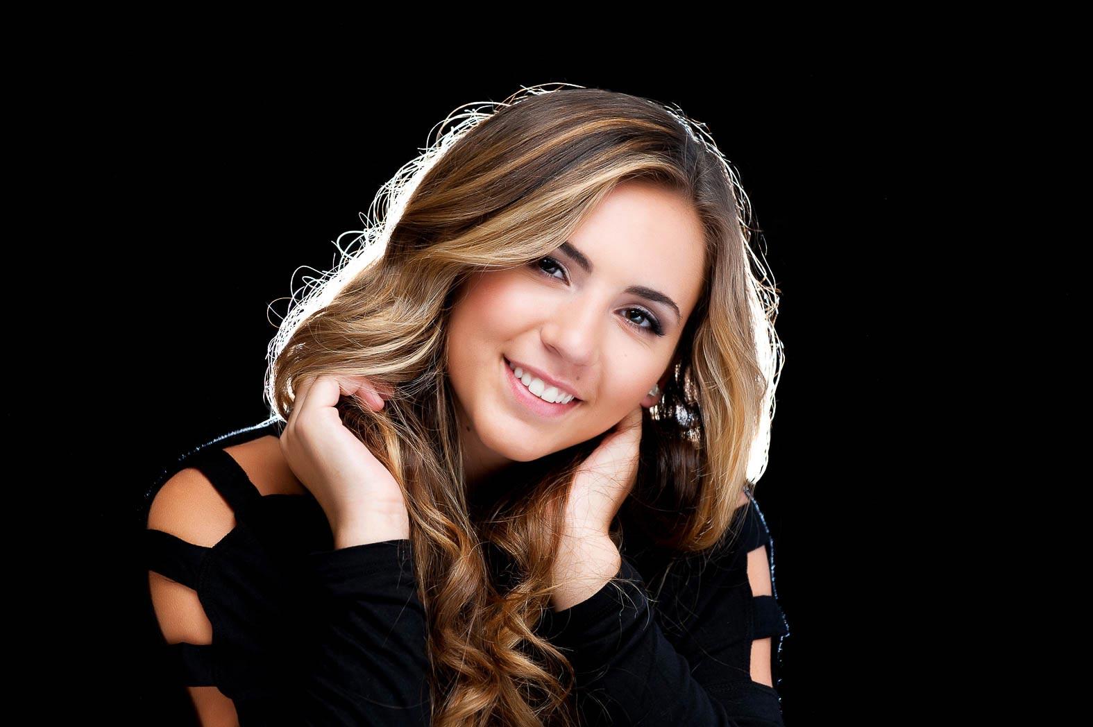 backlit senior picture of girl smiling in front of black background