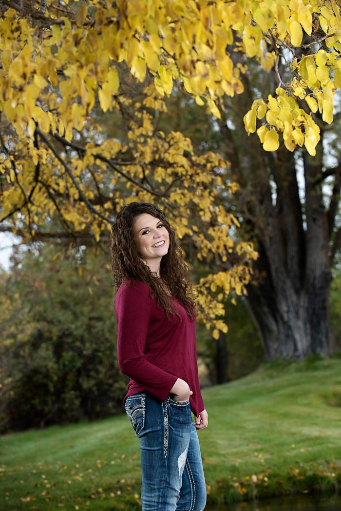 girl-standing-by-autumn-leaves-during-rainy-day-senior-pictures