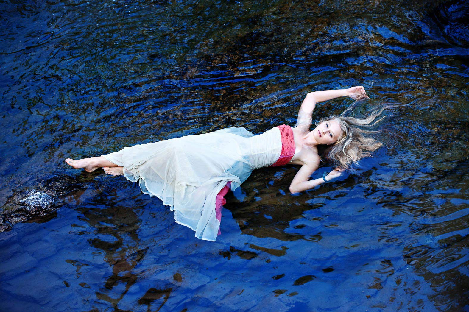 girl-wearing-formal-gown-floating-in-river-enchanted-senior-pictures
