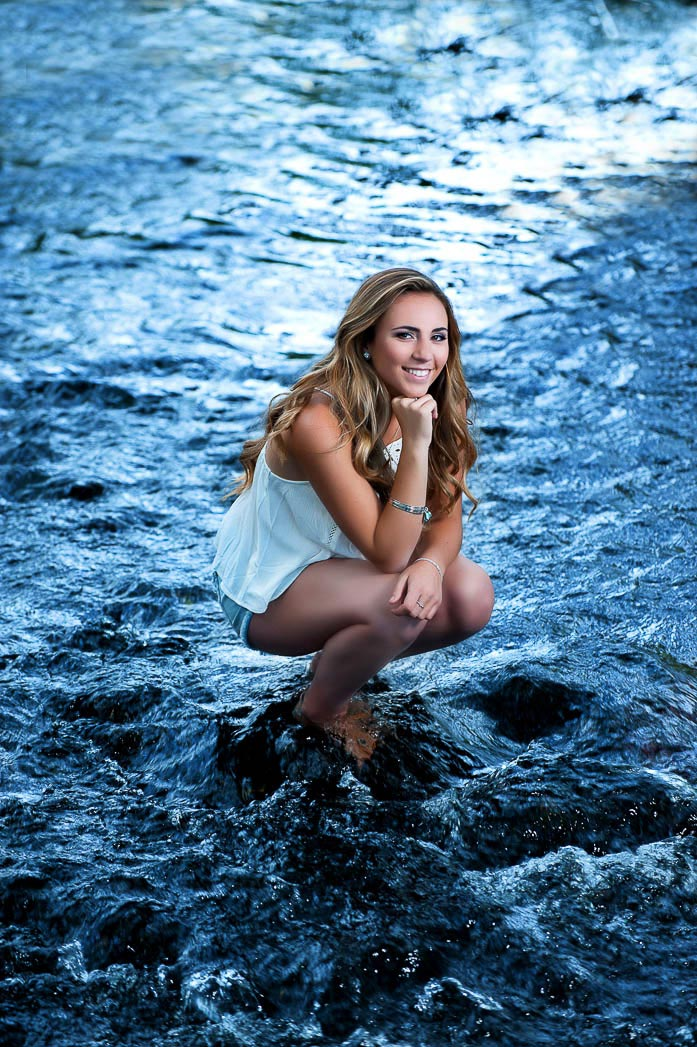 senior picture of girl crouching on rock in river