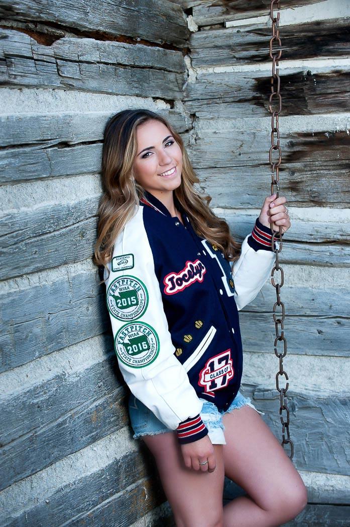 girl leaning against cabin wall wearing lettermans jacket