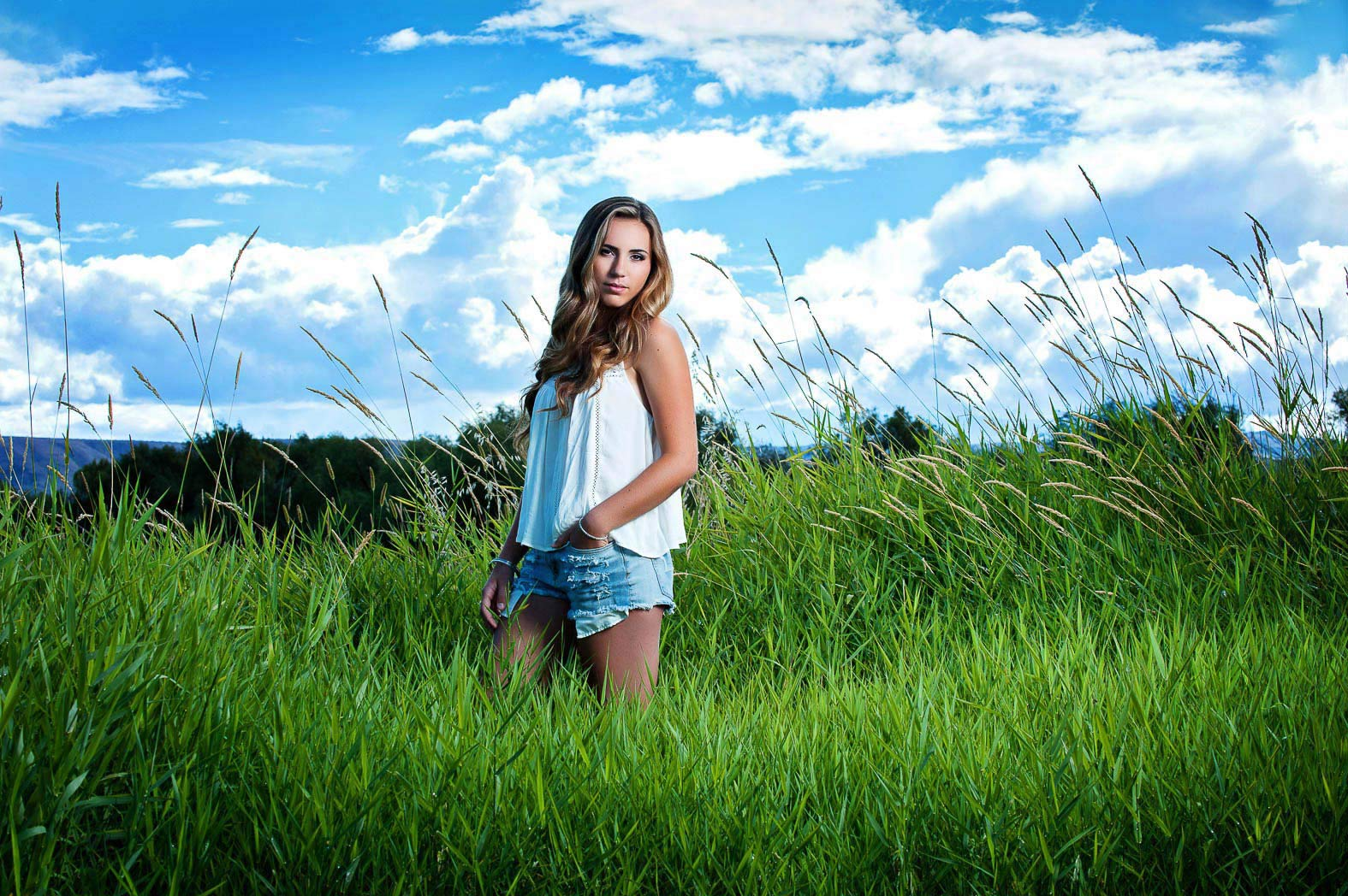 girl standing in tall green grass with cloudy sky behind during country senior pictures