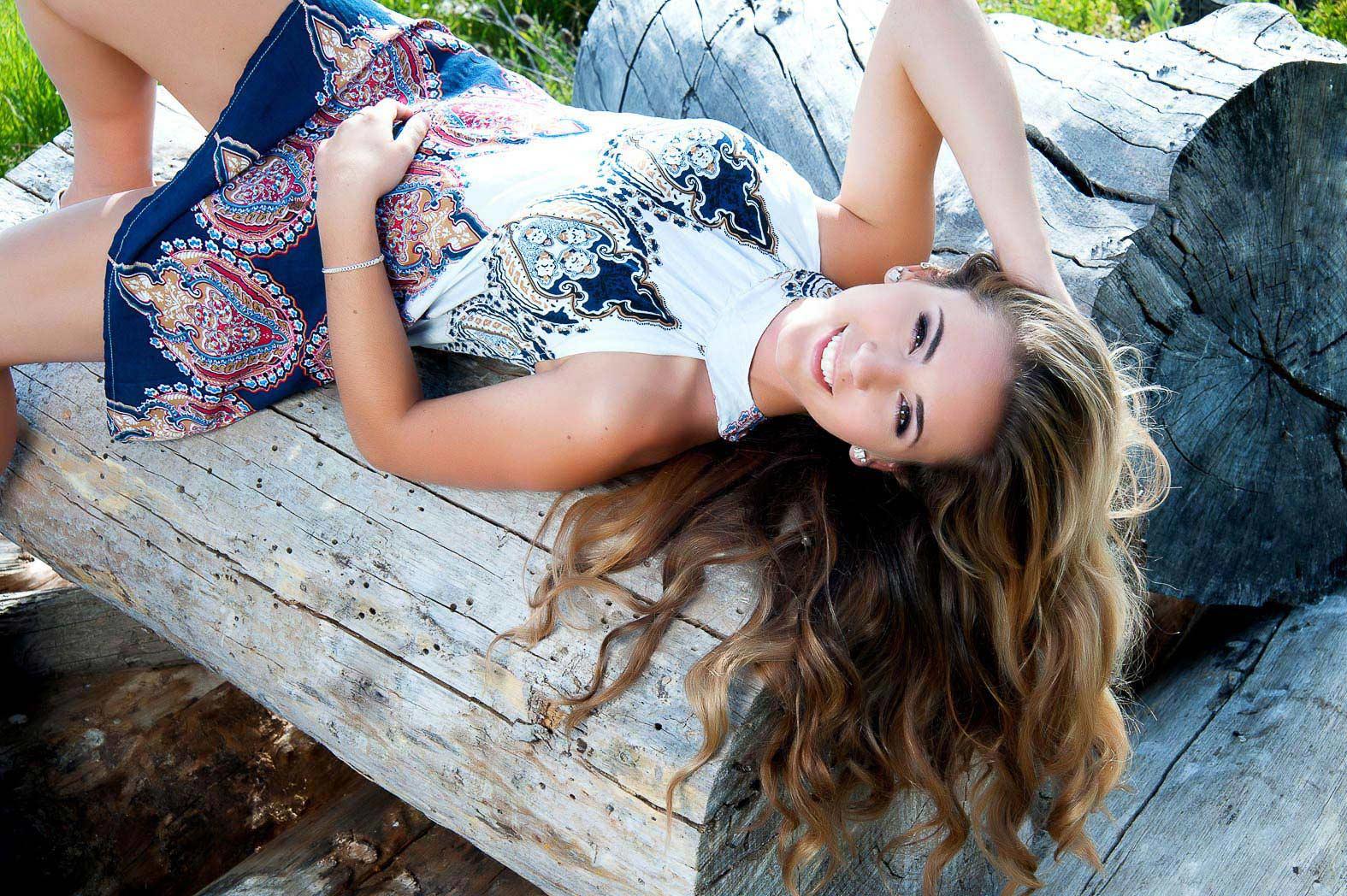 senior girl laying on log smiling up at camera