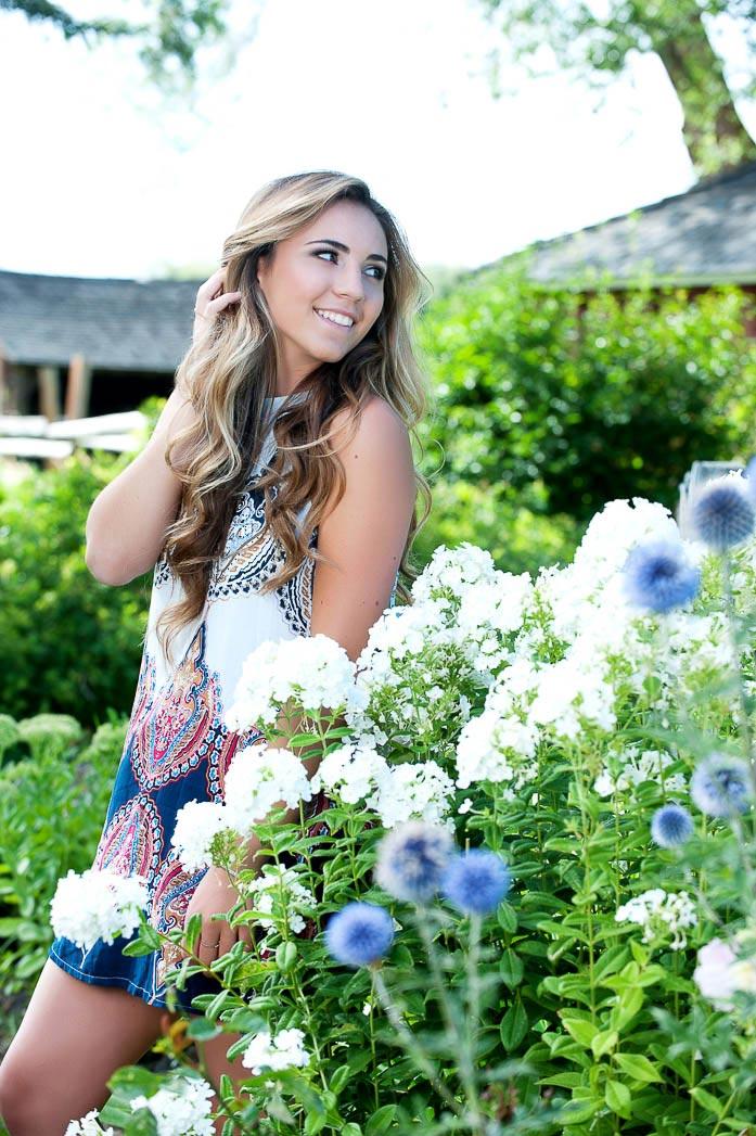 girl standing in garden looking over shoulder for senior picture posing