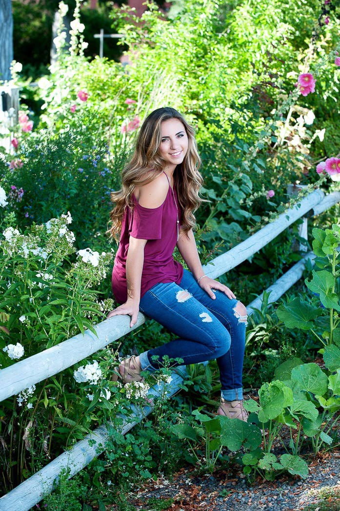 senior portrait of girl sitting in garden of flowers