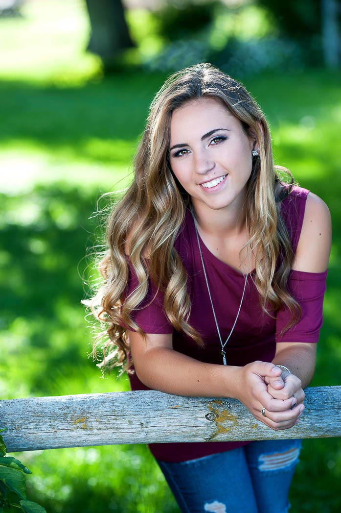 traditional senior picture girl leaning on fence
