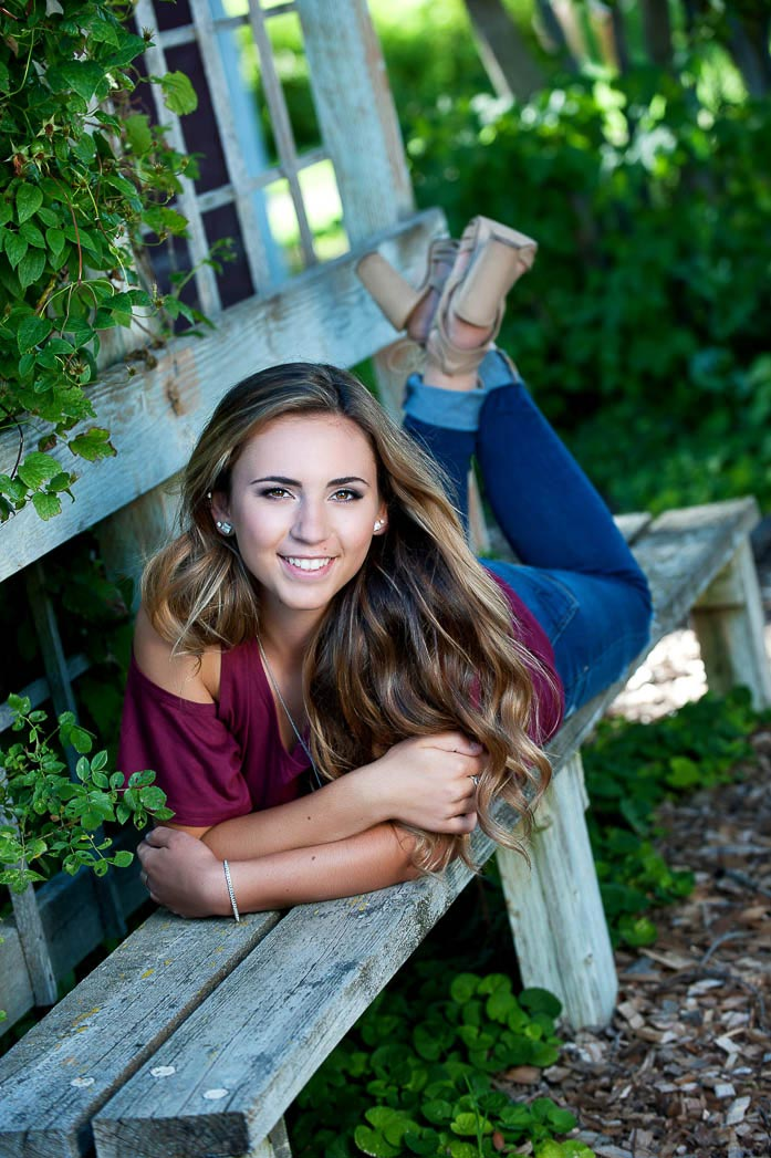 senior picture of girl laying on wooden bench