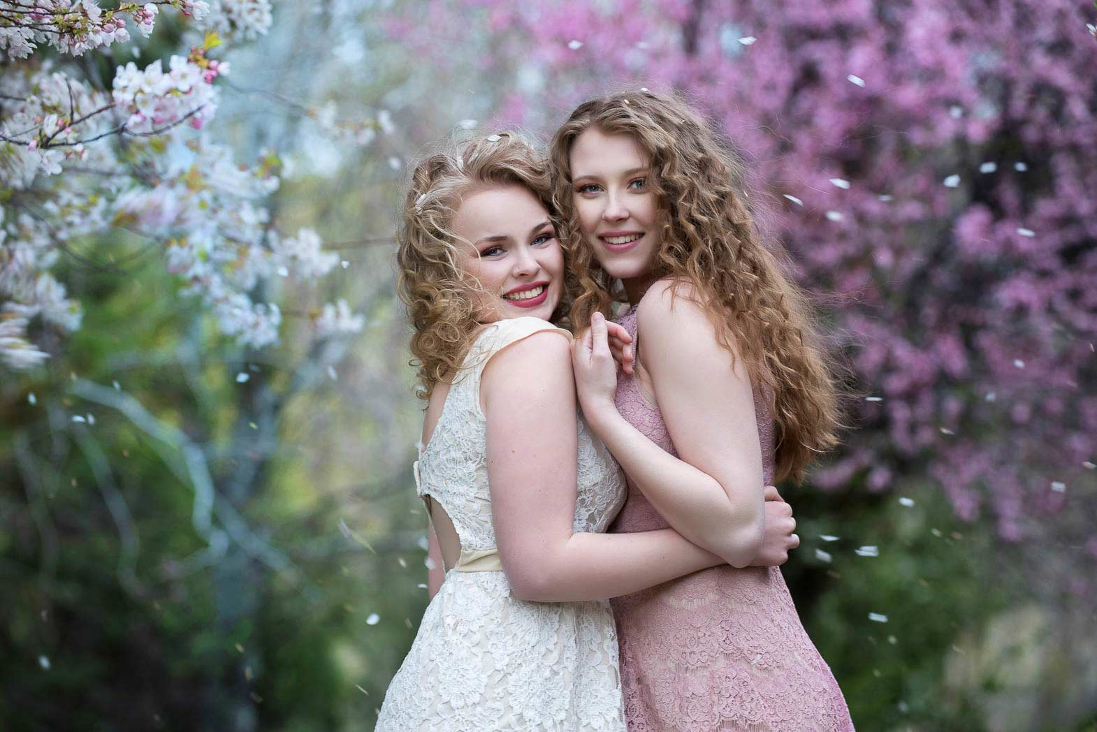 girls hugging as flowers blow past in wind during senior model shoot
