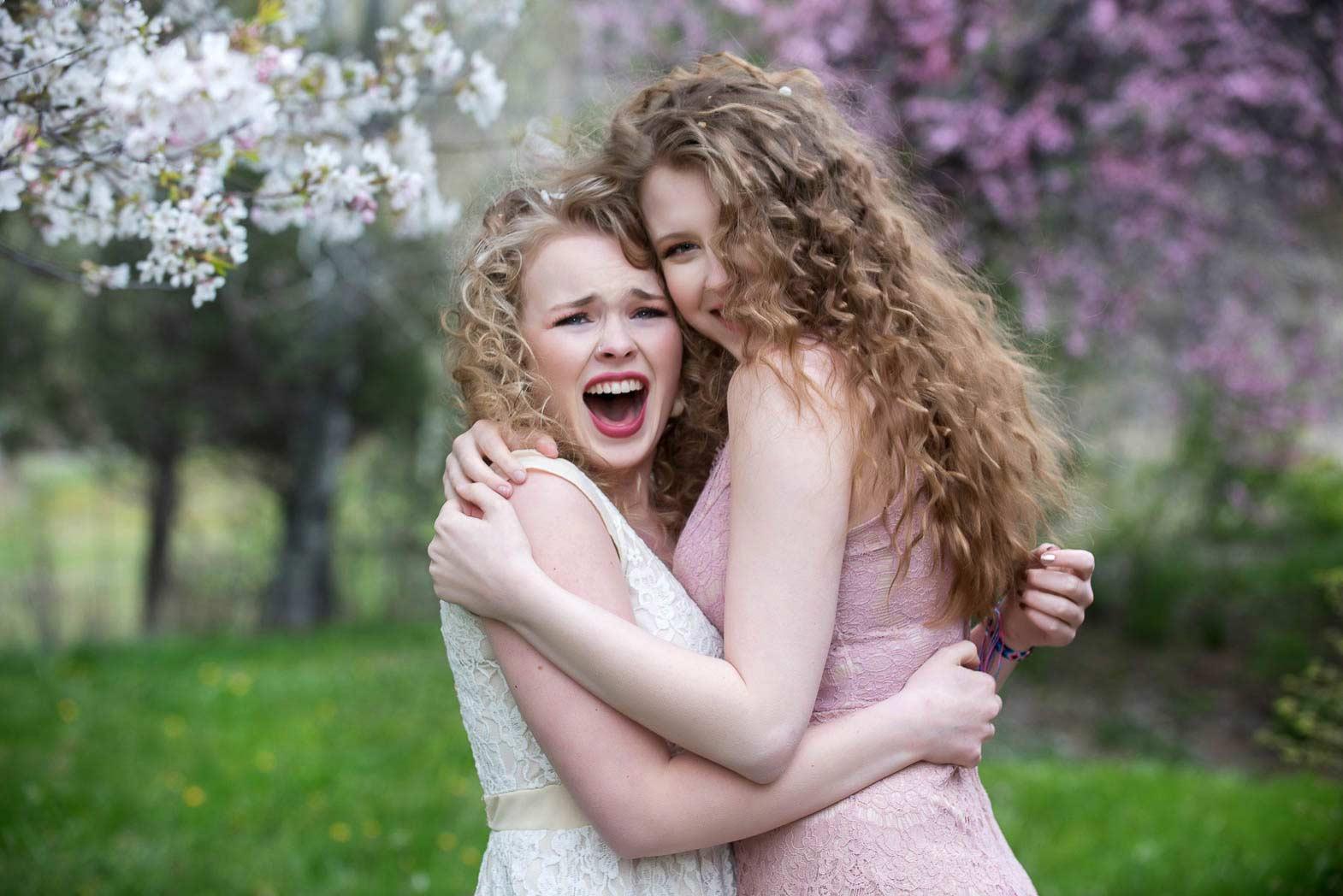 senior girls hugging and laughing among flowers during senior model shoot