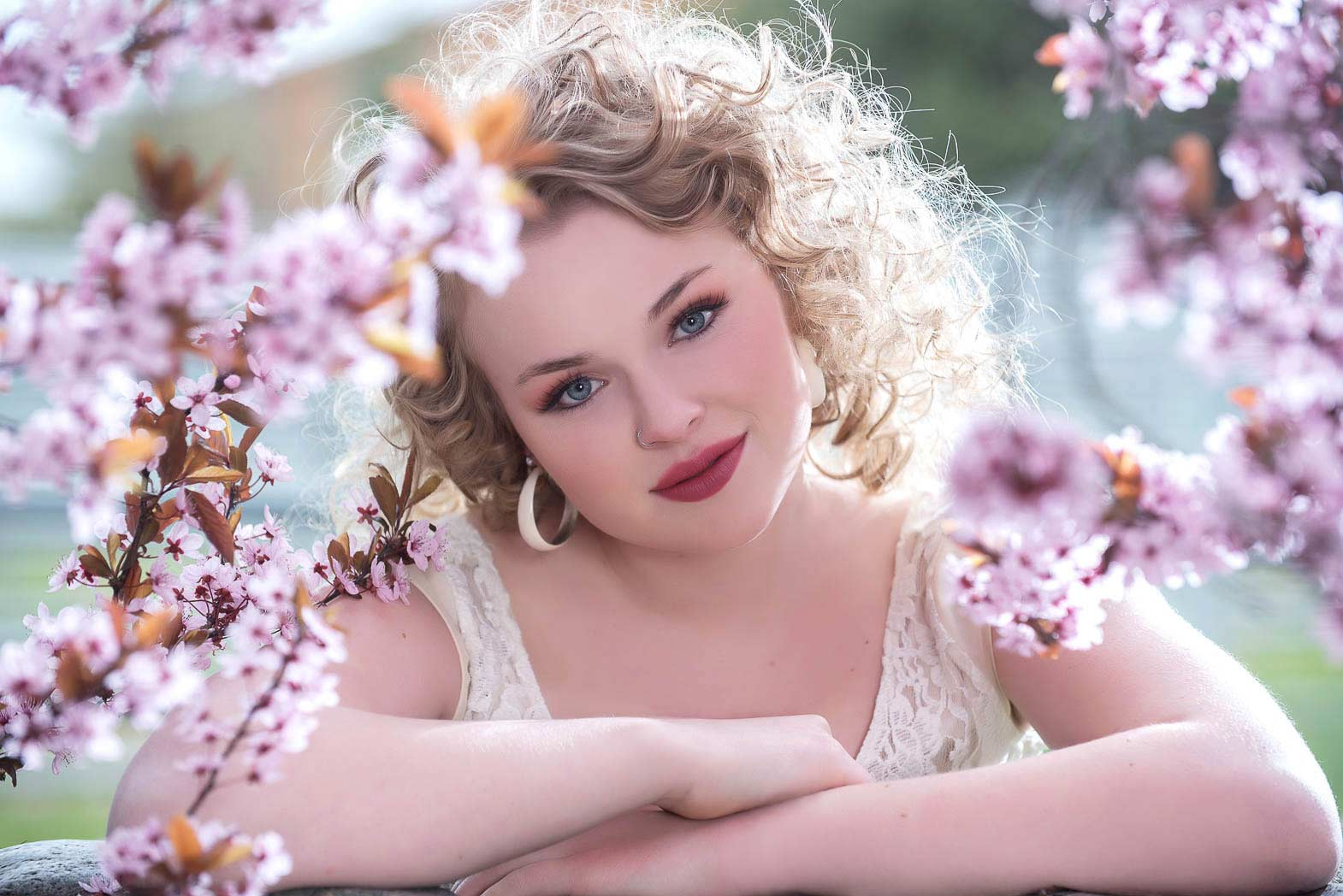 Senior girl model surrounded by pink flowers smiling