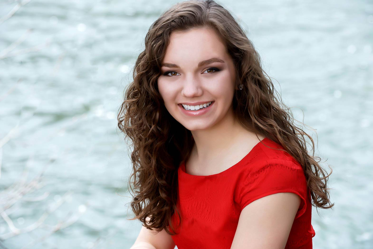 senior portraits of girl by river smiling