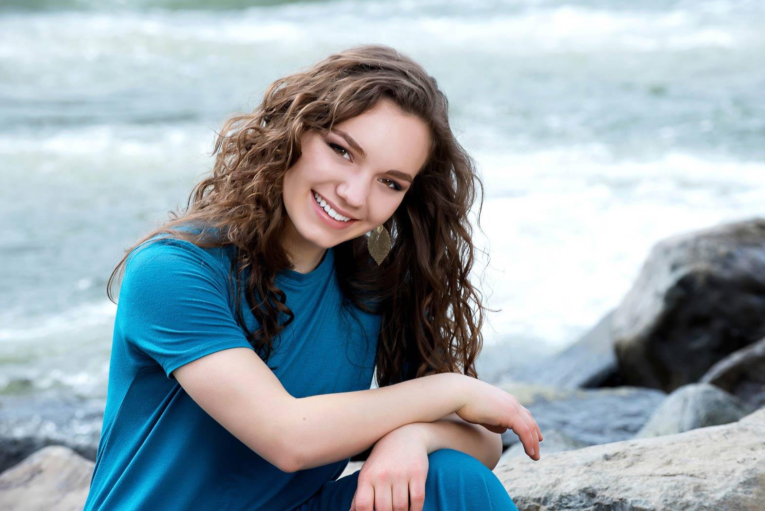senior portrait of girl smiling sitting by river